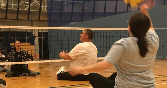 player serving in a game of sitting volleyball