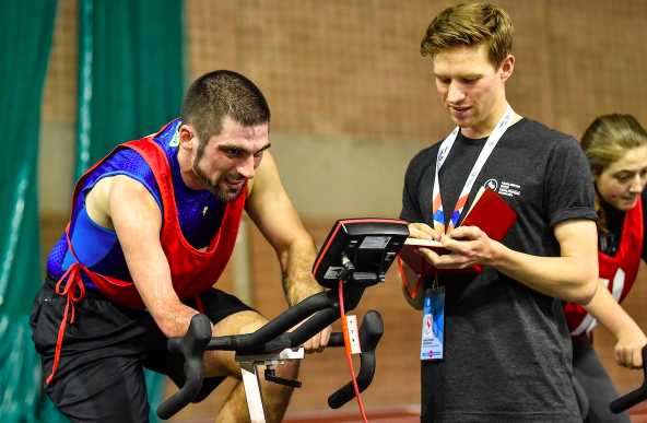 disabled athlete riding an erg bike with evaluator looking on